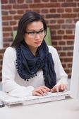 Serious casual young woman using computer — Stock Photo