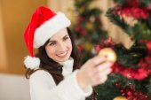 Happy brunette decorating a christmas tree — Stock Photo