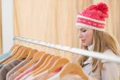 Close up of a pretty blonde looking at clothes on rail — Stok fotoğraf