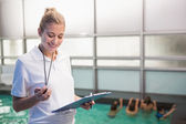 Pretty swimming coach standing poolside — Stock Photo