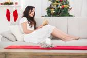 Relaxed brunette reading on the couch at christmas — Stock Photo