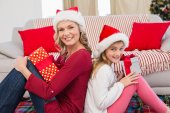 Festive mother and daughter smiling at camera with gifts — Stock Photo