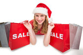 Smiling woman lying between sale shopping bags — Stockfoto