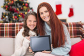 Festive mother and daughter showing tablet on the couch — Stock Photo