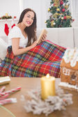 Smiling brunette reading on the couch with cover  — Stockfoto