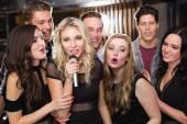 Happy friends singing karaoke together — Stockfoto