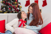 Festive mother and daughter on the couch with gift — Stock Photo