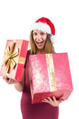 Surprised pretty brunette in santa hat opening gift — Stock Photo