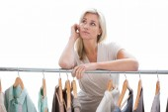 Pretty blonde looking through clothes rail — Stok fotoğraf