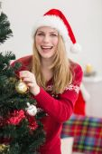 Smiling woman hanging christmas decorations on tree — ストック写真