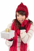 Surprised young woman holding a wrapped gift — Stock fotografie