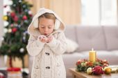 Festive little girl blowing over hands — Stock Photo