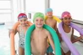 Kids standing poolside with foam rollers — Stock Photo
