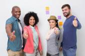 Creative team gesturing thumbs up at office — Stock Photo