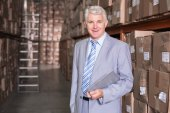 Warehouse manager smiling at camera in a warehouse — Stock Photo