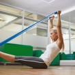 Side view of woman using resistance band in fitness studio — Stock Photo #60654757