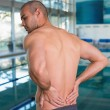 Rear view of shirtless swimmer with back ache by pool — Stock Photo #60655029