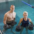 Swimmers working out with foam dumbbells in swimming pool at lei — Stock Photo #60655323
