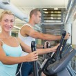 Side view of a fit young couple working on x-trainers at the gym — Stock Photo #60657295