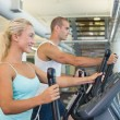 Fit young couple working on x-trainers at gym — Stock Photo #60657303