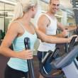 Fit young couple working on x-trainers at gym — Stock Photo #60657327
