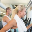 Side view of couple working on x-trainers at gym — Stock Photo #60657357