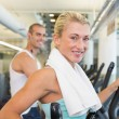 Fit young couple working on x-trainers at gym — Stock Photo #60657363