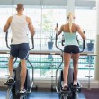 Rear view of couple working on x-trainers at gym — Stock Photo #60657369