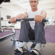 Fit man working out on rowing machine — Stock Photo #60658819