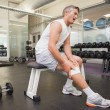 Injured man gripping his knee in the weights room — Stock Photo #60659151