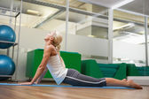 Side view of woman stretching her back in fitness studio — Stock Photo