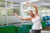 Smiling young woman doing power fitness exercise — Stock Photo