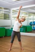 Full length of a sporty woman doing power fitness exercise — Stock Photo