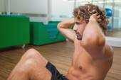 Side view of shirtless man doing push ups in gym — Stock Photo
