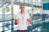 Swimming coach gesturing thumbs up by pool at leisure center — Stock Photo