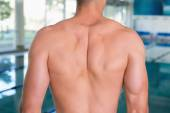 Mid section of a shirtless fit swimmer by pool at leisure center — Stock Photo
