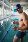 Swimmer gesturing thumbs up by pool at leisure center — Stock Photo
