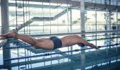 Side view of swimmer diving into pool at leisure center — Stock Photo