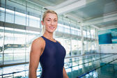 Smiling female swimmer by pool at leisure center — Foto de Stock