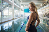 Fit female swimmer by pool at leisure center — Stock Photo