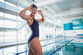 Portrait of female swimmer by pool at leisure center — Stock Photo
