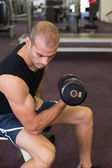 Young man exercising with dumbbell in gym — Stock Photo