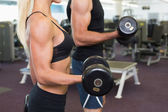 Mid section of couple exercising with dumbbells in gym — Stock Photo