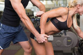 Male trainer assisting woman with dumbbell in gym — Stock Photo