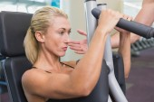 Fit young woman using fitness machine at gym — Stock Photo