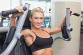 Fit woman using fitness machine at gym — Stock Photo