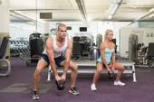 Fit couple lifting kettle bells in gym — Stock Photo