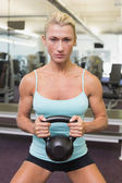 Serious woman lifting kettle bell in gym — Stock Photo