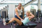 Male trainer assisting woman with abdominal crunches at gym — Stock Photo