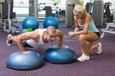 Trainer assisting man with push ups at gym — Stock Photo